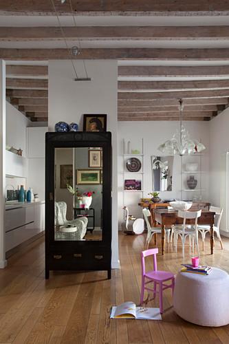 Schrank mit Spiegel im offenen Wohnraum mit Balkendecke