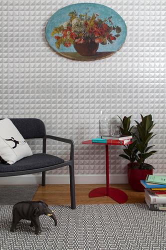 Moderner Stuhl und roter Beistelltisch vor grafischer Tapete