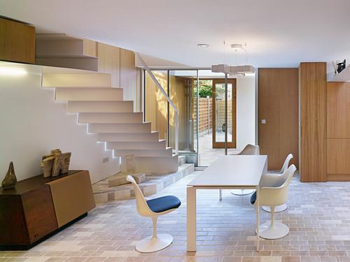 Weißer Tisch mit Klassikerstühlen auf Steinfliesen, im Hintergrund Treppe