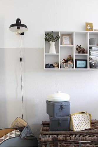 Vintage-style metal boxes and makeup bag on old wicker trunk, wall-mounted shelves and standard lamp