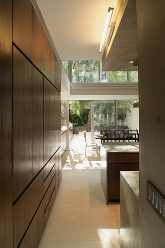 View from modern fitted kitchen into dining room and through into courtyard