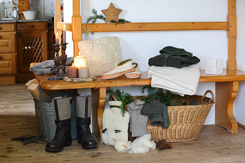 Knit fabrics and rustic wintry accessories on stove bench in cabin parlour