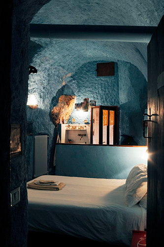 Rustic bedroom and ensuite bathroom with blue walls