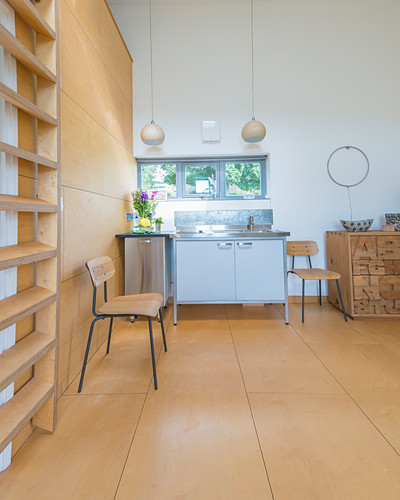 Kitchenette in open-plan interior with plywood floor