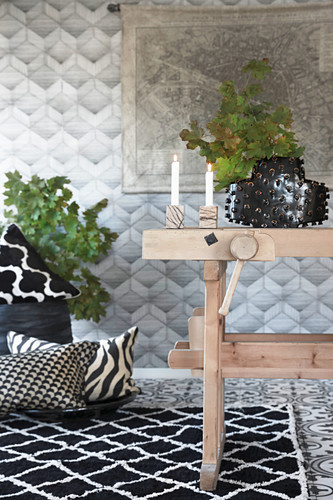 Rustic wooden table, black-and-white rug and cushions
