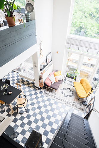 View from gallery down staircase into bright, open-plan living space