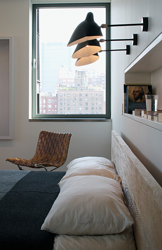 Three wall-mounted lamps and shelf in niche above double bed in front of designer chair below window in bedroom