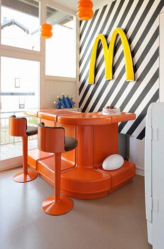 Orangefarbene Theke mit Barhockern vor schwarz-weiß gestreifter Wand mit Deko-Buchstabe