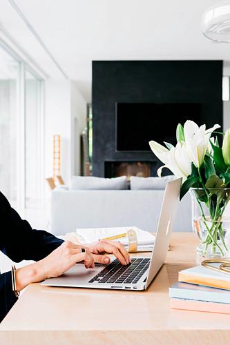 Laptop, Vase mit Blumen und Bücher auf hellem Schreibtisch
