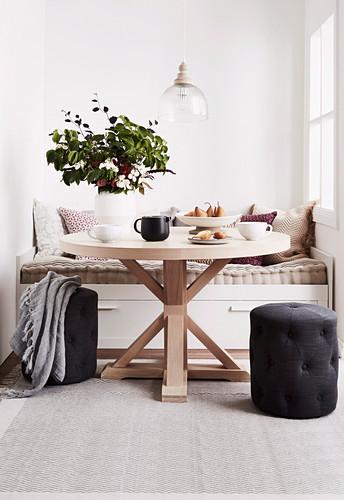 Runder Holztisch vor einer Bank in der Nische mit Fenster