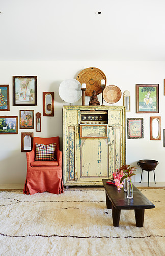 Japanese-style living room, chest of drawers with lanterns, chair with red cover and wooden bench, picture collection on the wall