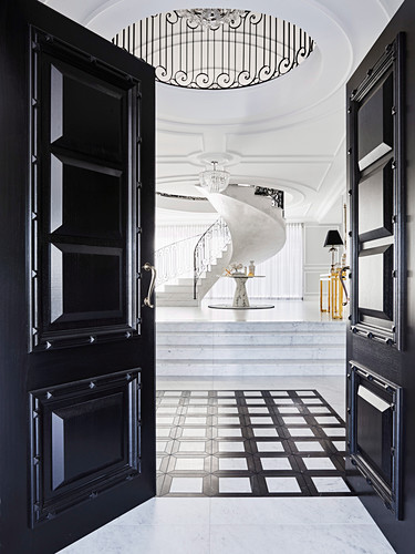 Glance into elegant hall with marble tiles and spiral staircase