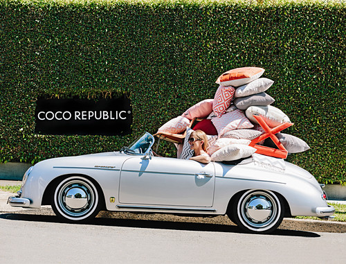 Frau sitzt im Cabrio mit voller Kissen