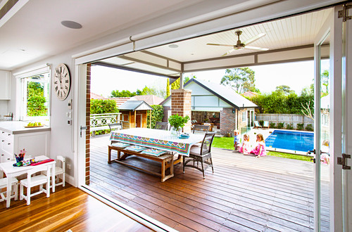 Blick auf Tisch mit Sitzbank und Stühlen auf Terrasse mit Holzdeck