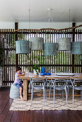 Long wooden table with classic chairs, pendant lights on the covered terrace above, boy sitting at the table