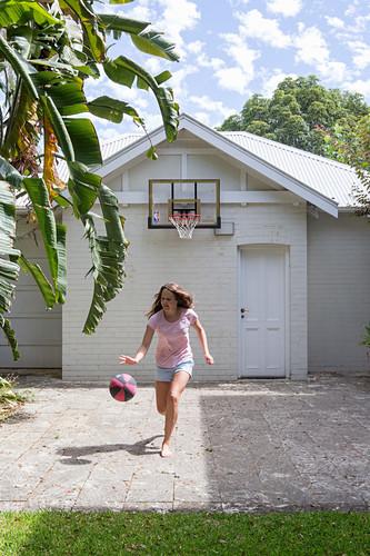 Mädchen spielt mit Basketball auf Vorplatz