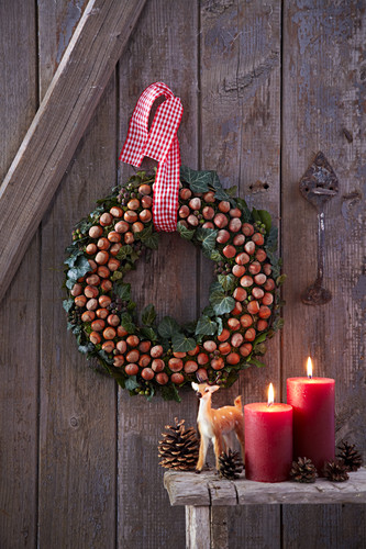 Festive wreath of hazelnuts and ivy on wall