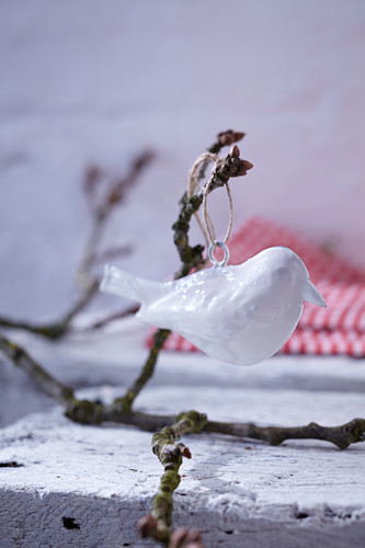White bird ornament hung from branch as wintry garden decoration
