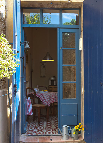 View through open French windows with blue-painted frame into kitchen-dining room