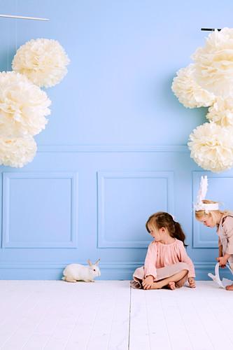 Zwei Mädchen mit einem Häschen im Raum mit hellblauer Wand