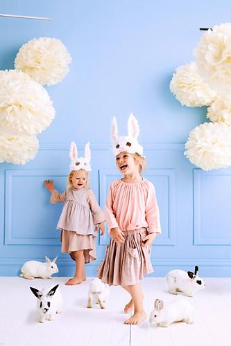 Zwei Mädchen mit DIY-Hasen-Masken und lebendigen Häschen im Raum mit hellblauer Wand