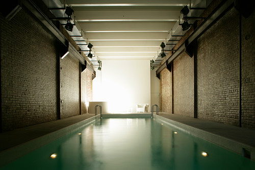 Swimming pool in room with brick walls
