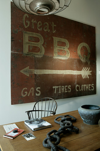 Altes Schild für Barbecue über dem Holztisch mit Kunsobjekt