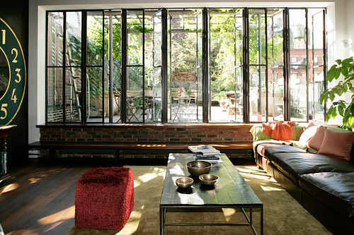 Sunny living room with glass wall overlooking roof terrace