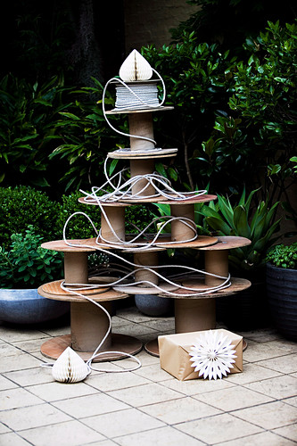 Large, old wooden spools in the shape of a Christmas tree arranged on the terrace