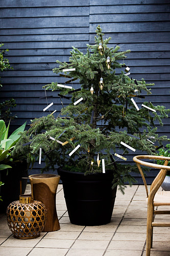 Small Christmas tree with DIY paper garland in the pot on the terrace