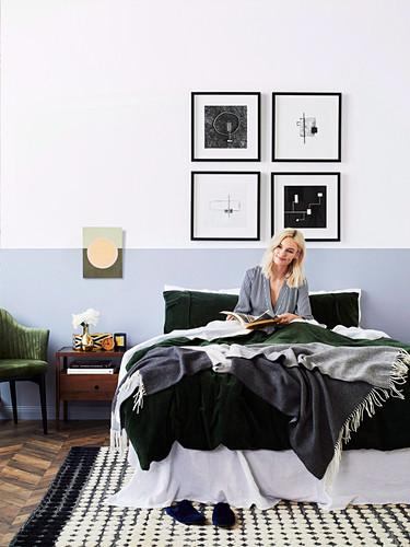 Junge Frau mit Buch im Bett, gerahmte Kunstwerke an der Wand