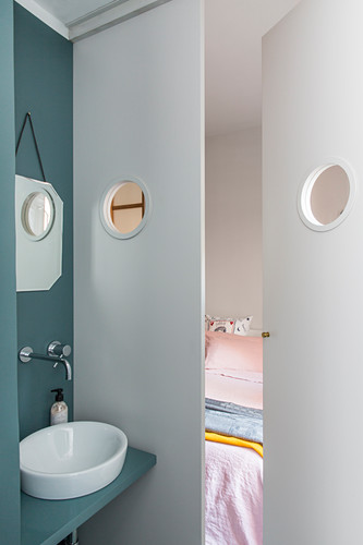 View from bathroom into bedroom through double doors with porthole windows