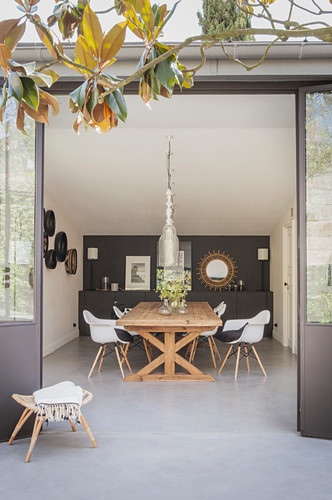View from terrace into dining room with wooden table and classic chairs