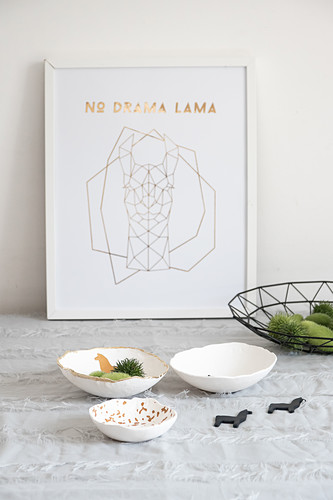 Handmade decorative bowls with lama motifs in front of framed drawing