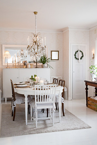 Festively decorated dining table below chandelier in Scandinavian dining room