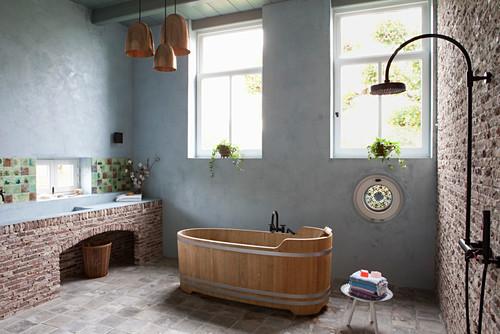 Free-standing wooden bathtub in bathroom of old farmhouse
