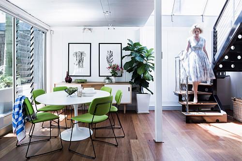 Replik von Klassikertisch mit limettengrünen Stühlen in offenem Essbereich, Frau auf Treppe