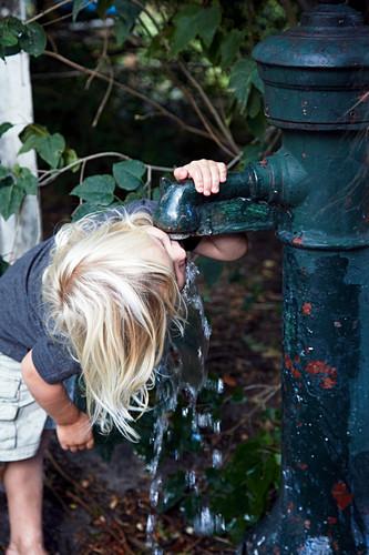 Blonde boy drinking from pump