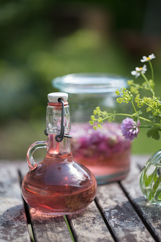 Homemade chive-flower vinegar in decorative carafe