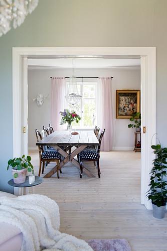 Blick durch geöffnete Schiebetür ins Esszimmer auf langen Tisch mit verschiedenen Stühlen