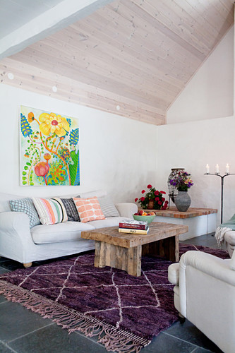 Colourful picture above in living room with exposed roof structure