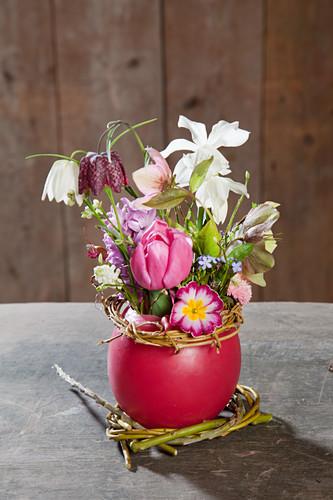 Spring flowers in red wax vase