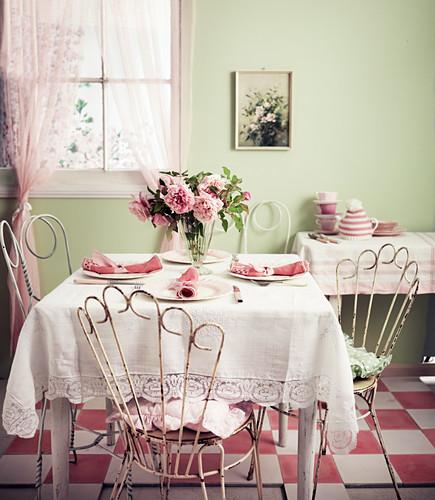 Rosafarbener Blumenstrauss auf rosa-weiss gedecktem Tisch