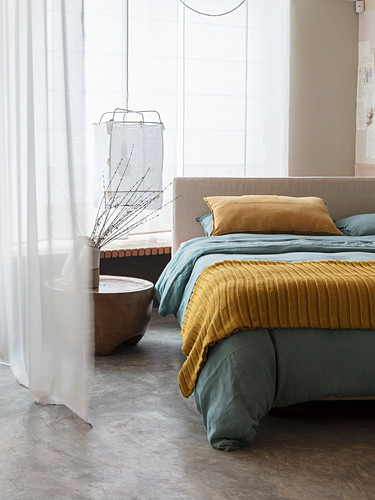Blick ins Schlafzimmer mit Doppelbett vor Fenster