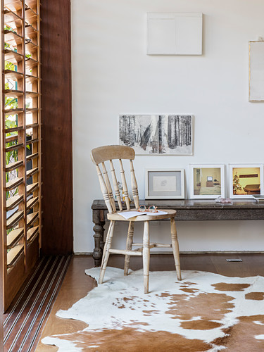 Collection of pictures on rustic wooden bench and wooden chair on cowhide rug next to window with louvre blinds