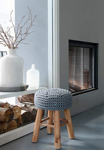 Stool with crocheted cover in front of stacked firewood and fireplace