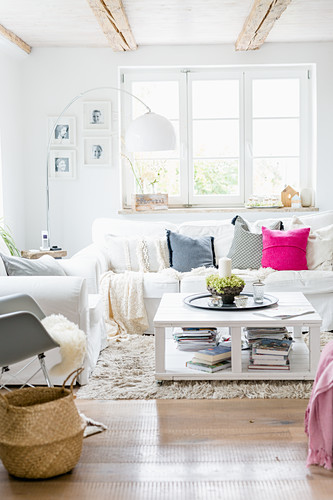 Country-house-style living room with white loose-covered furniture and coffee table