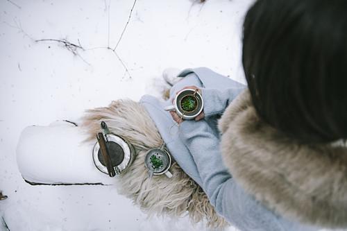 Frau trinkt Tee im verschneiten Garten