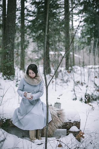 Frau trinkt Tee im verschneiten Wald