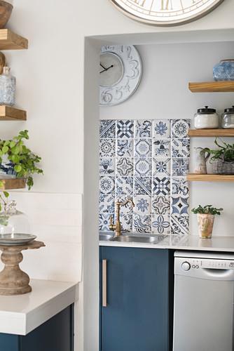 Blue-patterned tiles above sink in utility room